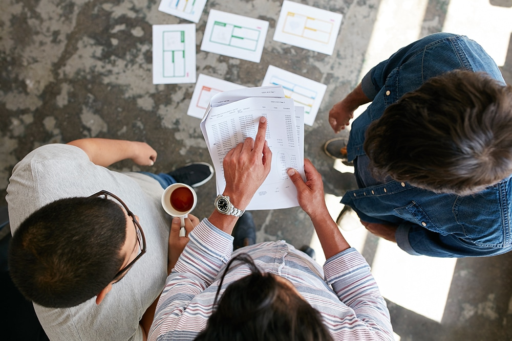 Top view of hands of three young people discussing financial transactions during a meeting. Man pointing at document while standing with colleagues in office. Business partners discussing financial data at meeting