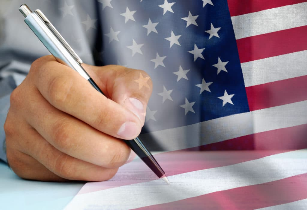 United States official signing an official document with a ballpoint pen with an overlay of the national flag the Stars and Stripes