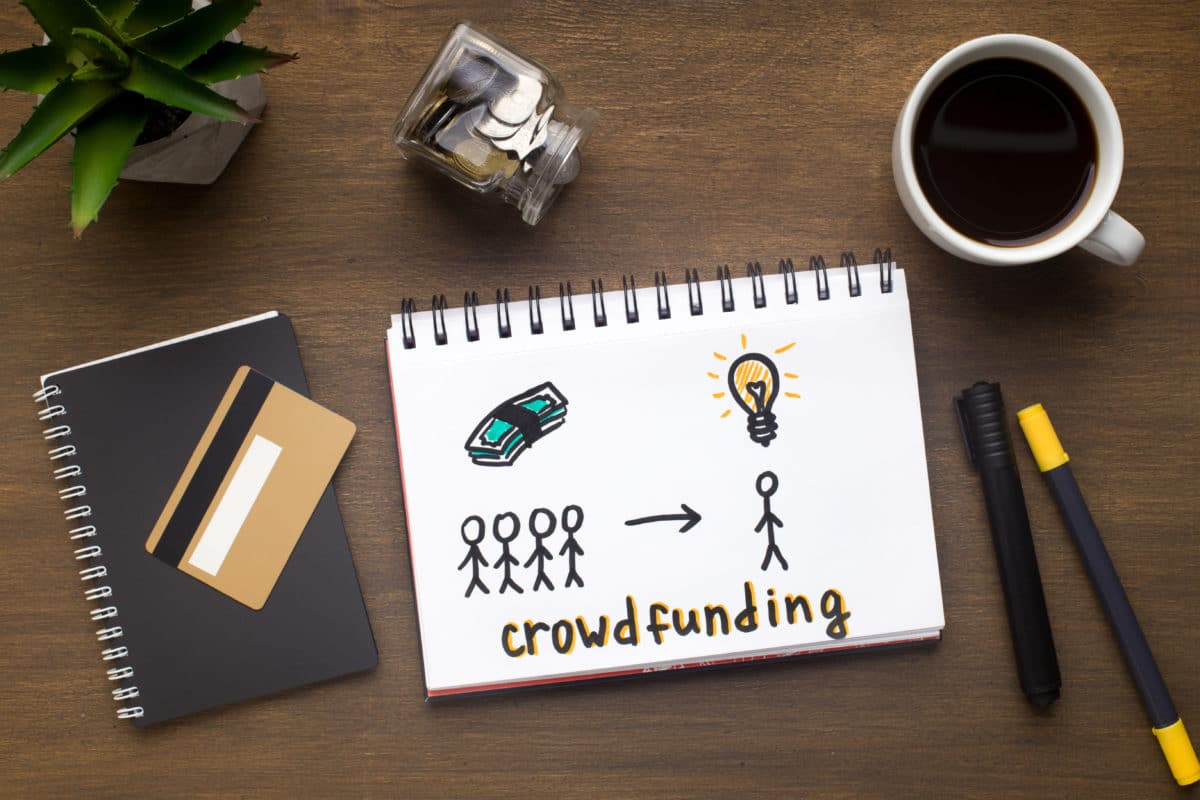 Drawing with crowdfunding concept in notepad, gold credit card and office supplies on wooden table, panorama
