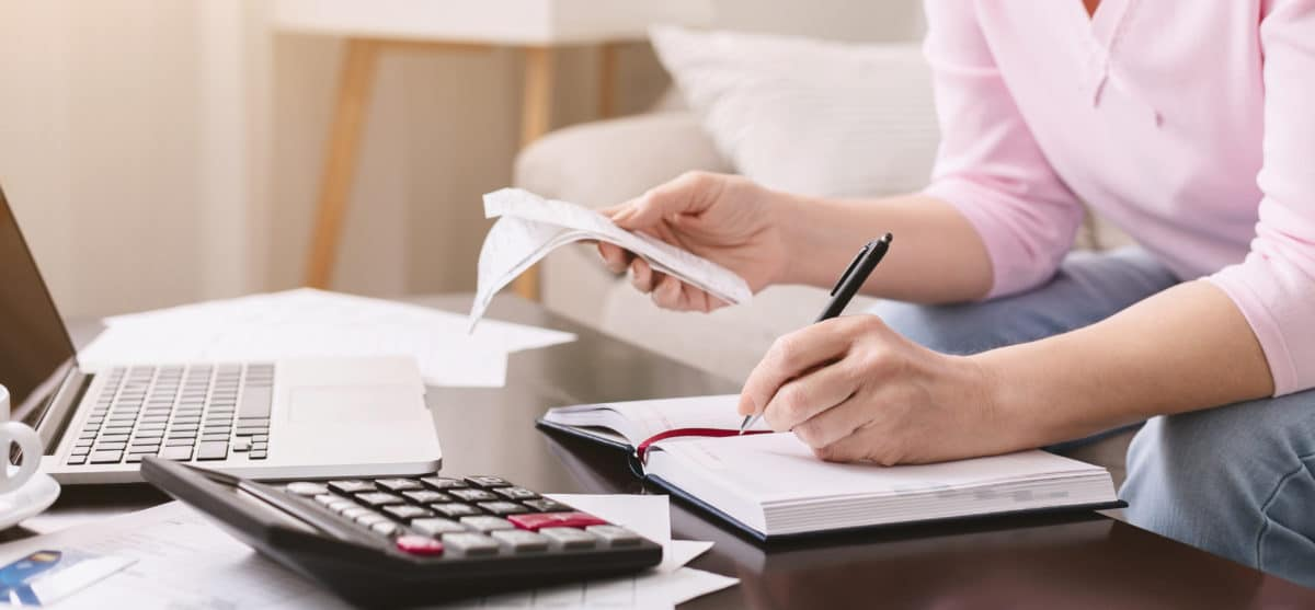 lady with bills noting her purchases at home