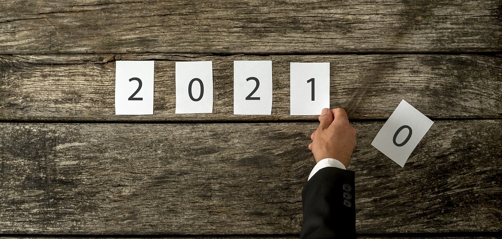 Male hand changing 2020 sign into 2021 assembled with white cards laid over a textured rustic wooden boards.